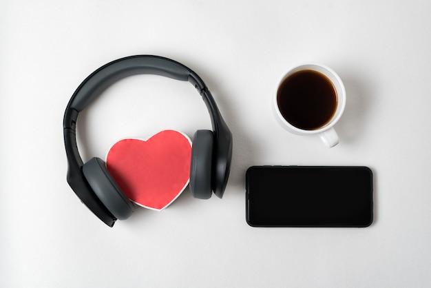 Pudełko w kształcie serca ze słuchawkami stereo, smartfonem i filiżanką herbaty na. widok z góry