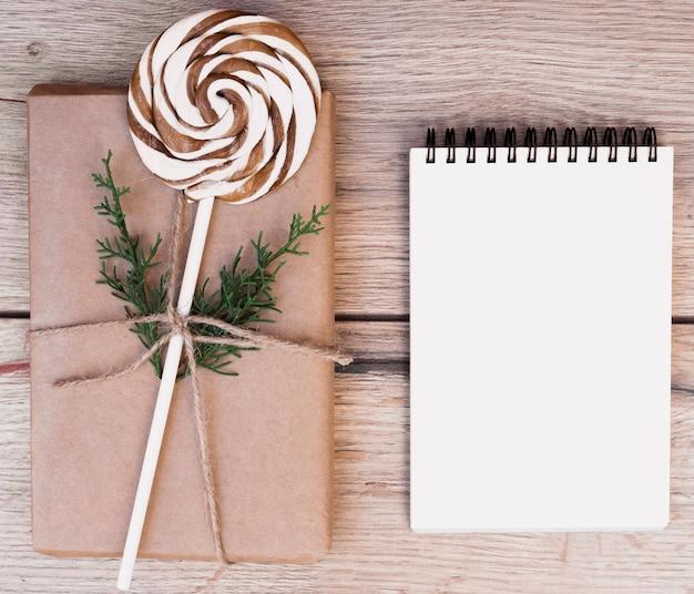 Pudełko w opakowaniu z lollipop w pobliżu notatnika