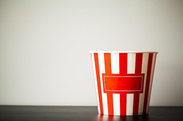Pudełko w paski z popcornem na drewnianym biurku