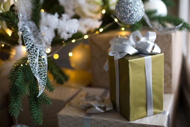 Pudełko w złotym opakowaniu i srebrna kokardka pod choinkę z białym zdobieniem. nowy rok, wigilia, pozdrowienia dla rodziny, pocieszenie i czekanie na cud