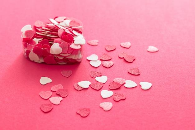 Pudełko wypełnione wieloma różowymi małymi sercami.