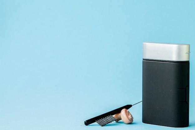 Pudełko z aparatem słuchowym i akcesoriami na kolorowym tle