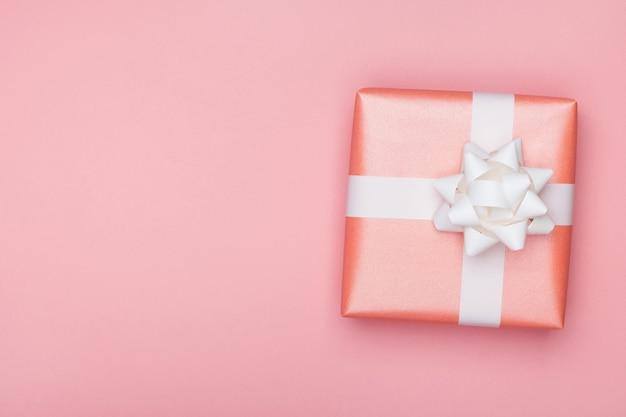Pudełko z białą kokardką na różowej powierzchni. urodziny lub rocznica z życzeniami