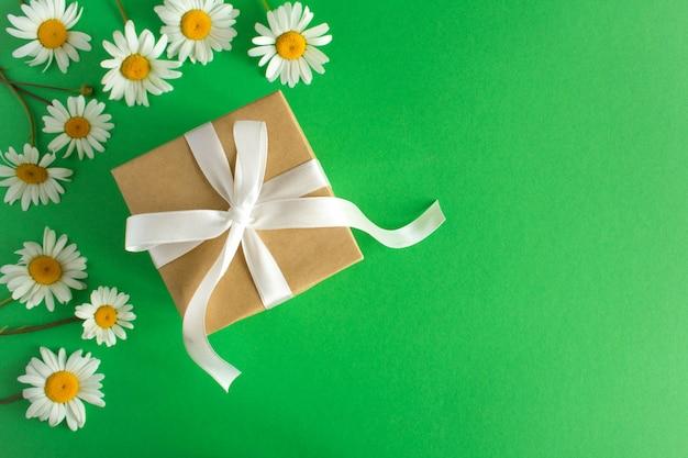 Pudełko z białą wstążką i rumiankiem na zielonym tle. widok z góry.