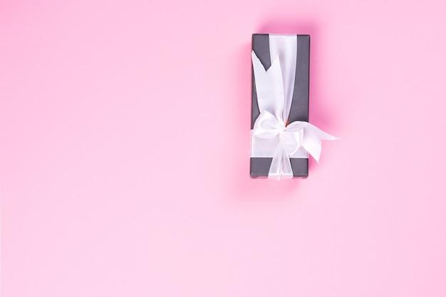 Pudełko z białą wstążką na różowym tle, płaskie leżał