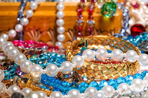 Pudełko z biżuterią, perłowe koraliki i różna inna wielokolorowa biżuteria, selektywne skupienie, koncepcja dobrobytu
