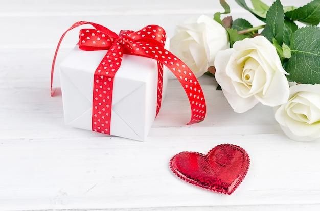 Pudełko z bukietem białej róży na białym drewnianym stole.