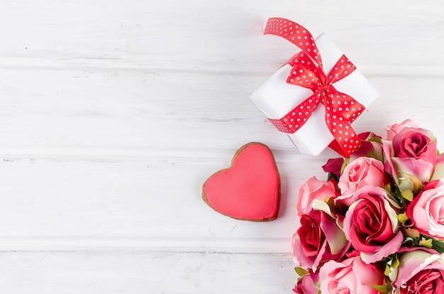 Pudełko z bukietem róż na białym drewnianym stole.