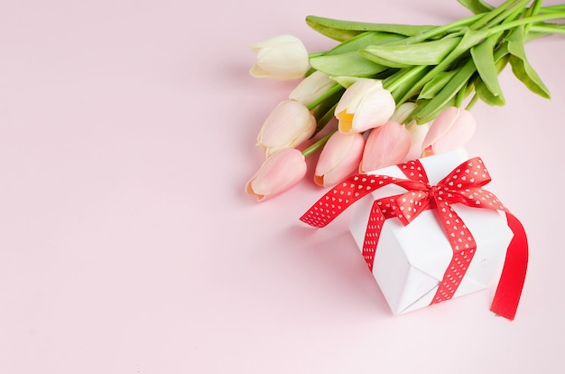 Pudełko z bukietem tulipanów na pastelowym różowym stole.