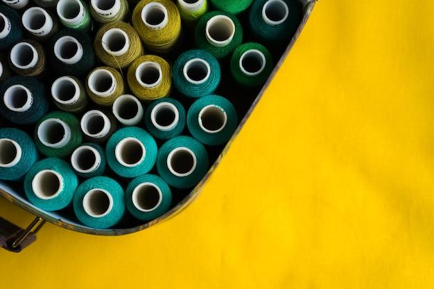 Pudełko z cewkami z kolorowymi nitkami na żółtym stole