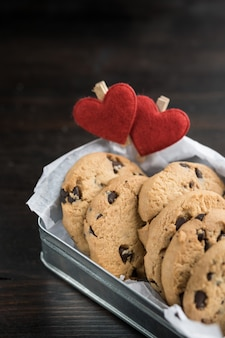 Pudełko z ciasteczka czekoladowe na stole z dwoma sercami szczypce. walentynki koncepcji.