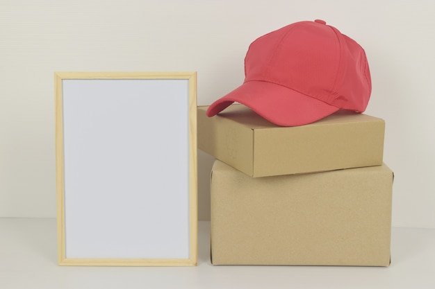 Pudełko z czapką z daszkiem i pustą ramką z boku
