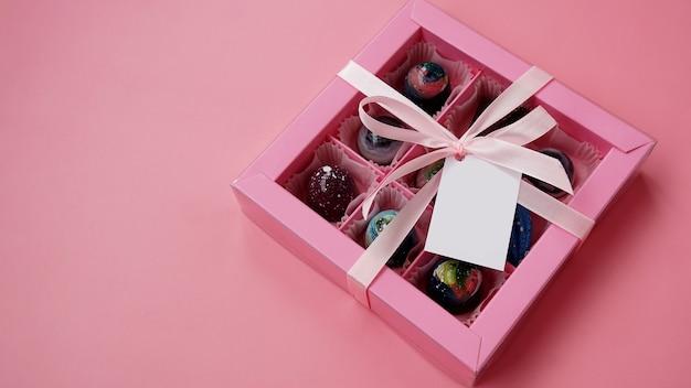 Pudełko z czekoladowymi cukierkami w kolorze różowym z ręcznie robionymi czekoladkami na różowo