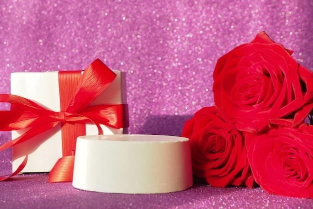 Pudełko z czerwoną kokardą i podium na fioletowym błyszczącym tle