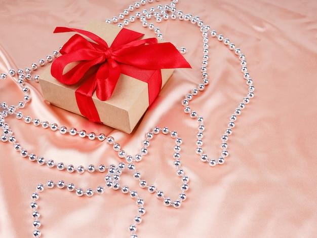 Pudełko z czerwoną kokardą, na tle nude satyna, koncepcja ślubu i bożego narodzenia.
