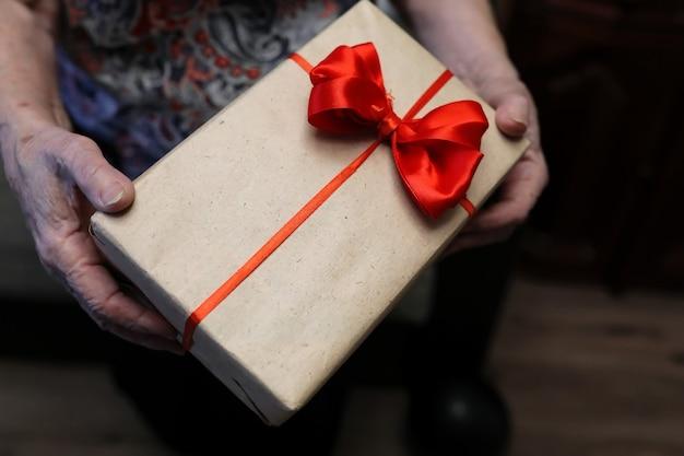 Pudełko z czerwoną kokardą w makro ręce babci