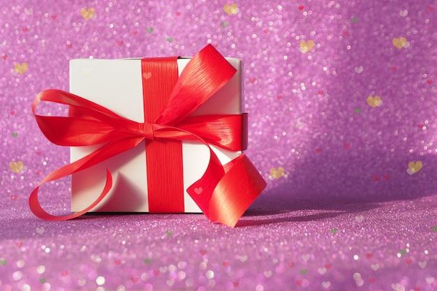 Pudełko z czerwoną kokardką na fioletowym błyszczącym tle