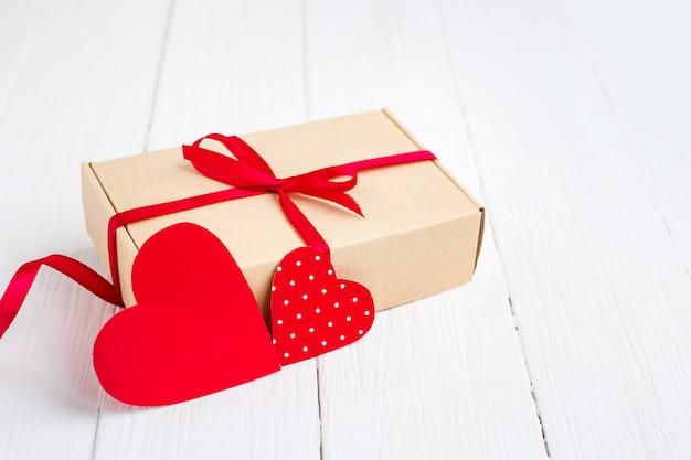 Pudełko z czerwoną wstążką, dwa czerwone serca na białym tle drewnianych. walentynki tło z kopii przestrzenią