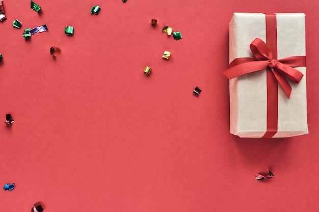 Pudełko z czerwoną wstążką i dekoracjami konfetti na pastelowym papierze kolorowe tło