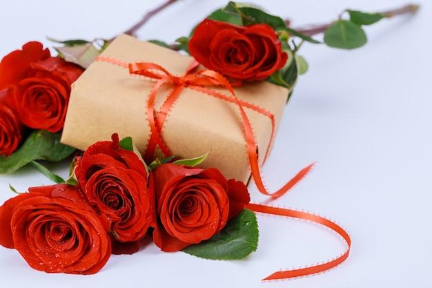 Pudełko z czerwoną wstążką i pięknymi czerwonymi różami. koncepcja walentynki.
