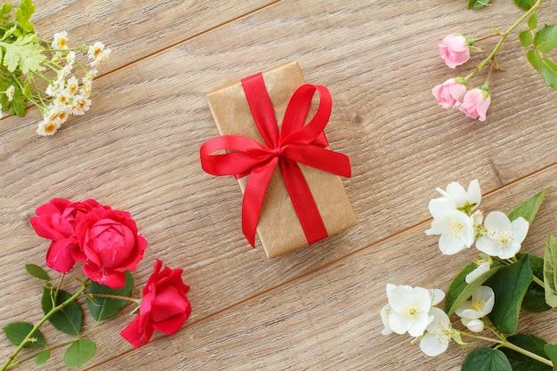Pudełko z czerwoną wstążką i pięknymi kwiatami róż, jaśminu i rumianku na drewnianym tle. koncepcja dawania prezentu na święta. widok z góry.