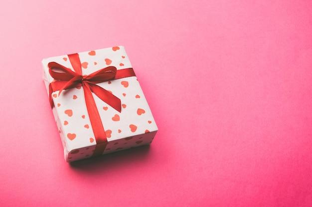 Pudełko z czerwoną wstążką i serca, widok z góry z miejsca kopiowania tekstu