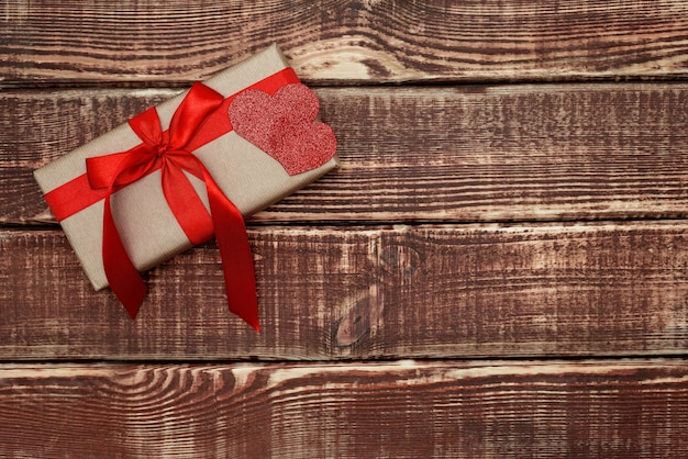 Pudełko z czerwoną wstążką i sercem na tle drewnianych. miękka selektywna ostrość. skopiuj miejsce.