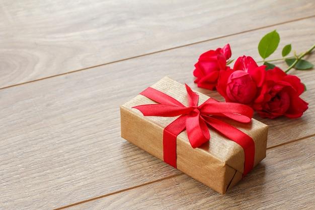 Pudełko z czerwoną wstążką na drewnianych deskach z bukietem czerwonych róż. widok z góry z miejsca na kopię.