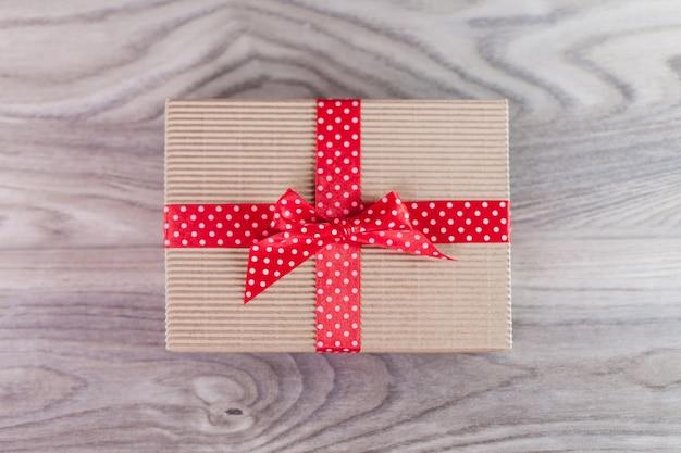 Pudełko z czerwoną wstążką na drewnie