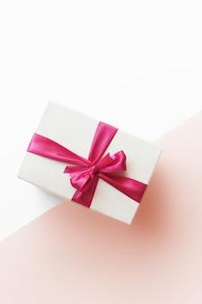 Pudełko z czerwoną wstążką na różowym tle