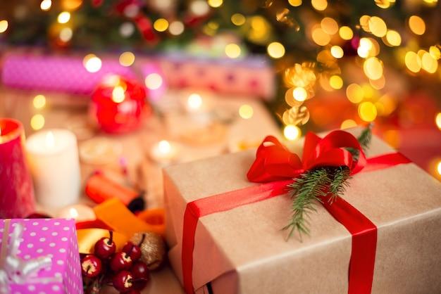 Pudełko z czerwoną wstążką na stole obok innych prezentów