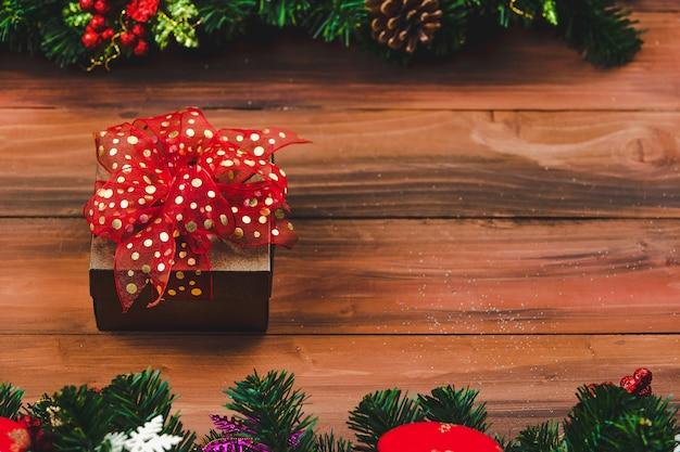 Pudełko z czerwoną wstążką na tle drewna z choinką i tradycyjnymi ozdobami rekwizyty bożonarodzeniowe z miejsca kopiowania. koncepcja szczęśliwego i radosnego festiwalu.
