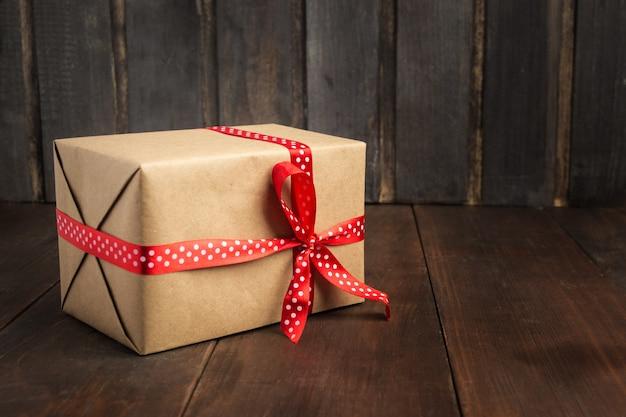 Pudełko z czerwoną wstążką na wakacje nad drewnianym stołem z miejscem na kopię