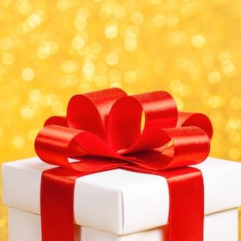 Pudełko z czerwoną wstążką na złotym tle