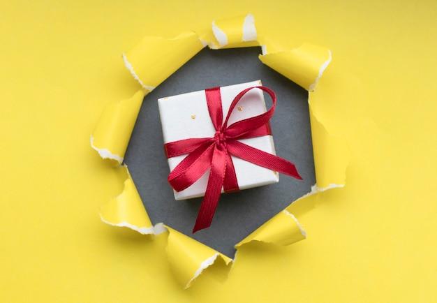 Pudełko z czerwoną wstążką, odizolowane na żółto