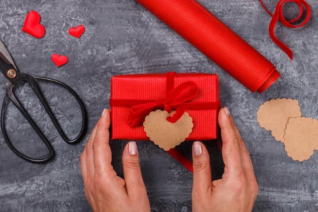 Pudełko z czerwoną wstążką. prezent świąteczny. walentynki. kartkę z życzeniami