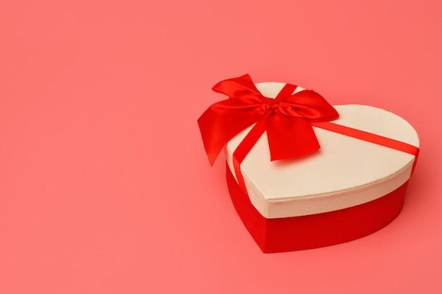 Pudełko z czerwoną wstążką w kształcie serca na różowym tle. walentynki