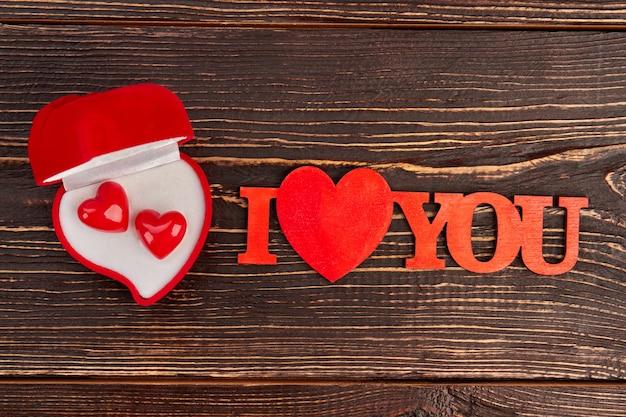 Pudełko z czerwonego aksamitu z kolczykami. walentynki tło napis kocham na brązowym tle drewnianych.