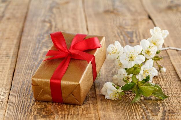Pudełko z czerwonymi wstążkami, gałąź pięknych kwiatów jaśminu na drewnianych deskach. koncepcja dawania prezentu na święta.