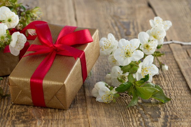 Pudełko z czerwonymi wstążkami, gałąź pięknych kwiatów jaśminu na starych drewnianych deskach. koncepcja dawania prezentu na święta.