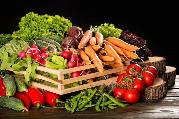 Pudełko z dojrzałymi warzywami na stole z ciężarówkami