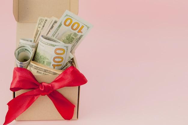 Pudełko z dolarów na różowym tle z bliska.
