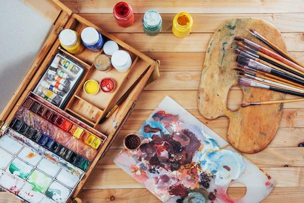 Pudełko z farbami akwarelowymi, pędzlami artystycznymi na płótnie.