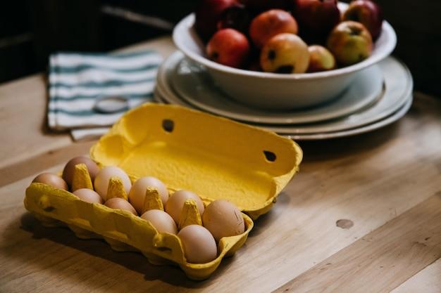 Pudełko z jajkami na drewnianym stole z miską jabłek na tle