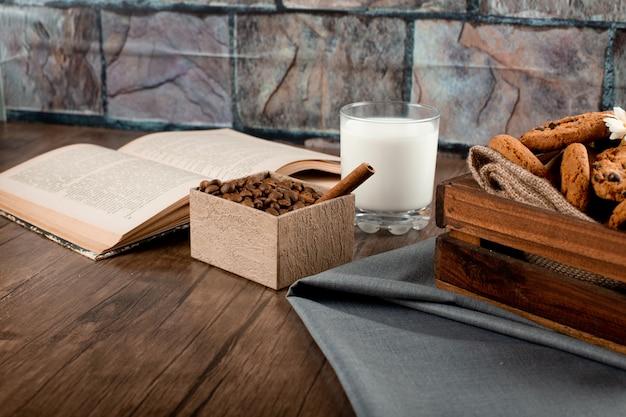 Pudełko z kawą, taca na ciastka, szklanka mleka i książka