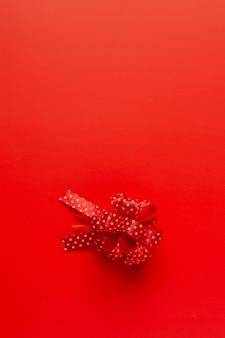 Pudełko z kokardą czerwoną wstążką na czerwonym tle