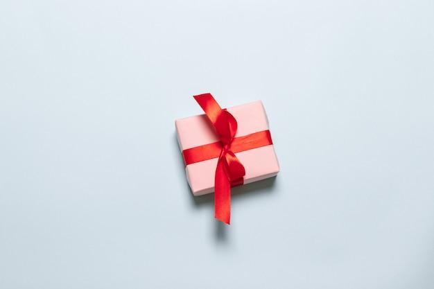 Pudełko z kokardą czerwony na niebieskim tle z miejsca na tekst