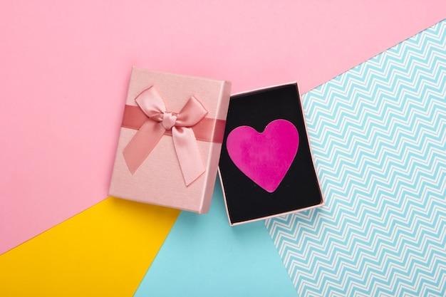 Pudełko z kokardą i ozdobnym sercem na kolorowym tle. walentynki. trend w pastelowych kolorach. widok z góry