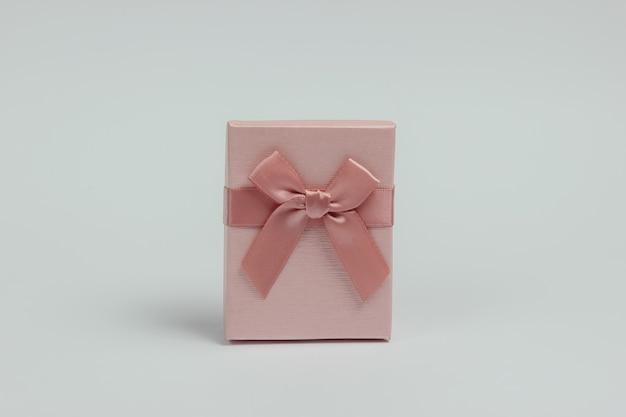 Pudełko z kokardą na białym tle. kompozycja na boże narodzenie, urodziny lub wesele.