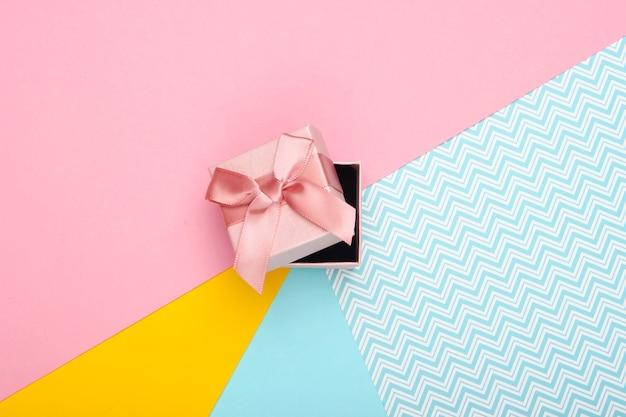 Pudełko z kokardą na kolorowym tle. trend w pastelowych kolorach. widok z góry